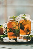 Summer refreshing cold peach ice tea with fresh mint leaves in glass jars on metal tray, selective focus