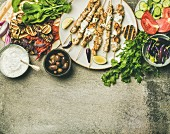 Flatlay of grilled chicken skewers with yogurt dip, flatbread, parsley, vegetables, marinated olives and chilis over grey concrete background