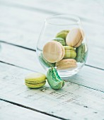 Colorful pastel pink, green and blue French macaron biscuits in glass over light blue painted wooden table