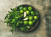 Flatlay of freshly picked organic limes and mint leaves for making cocktail or lemonade in wooden plate