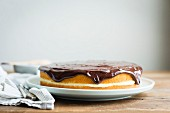 Vanilla layer cake with cream filling and chocolate sauce topping