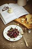 Beetroot and mint salad on a white plate with vintage cutlery and torn crusty bread on an olive wood chopping board, book, salt and pepper pots