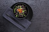 A bowl of black rice with miso mushrooms topped with chopped coriander, sesame seeds and red chilli. Served in a black bowl