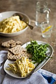 A pile of seasoned celeriac remoulade on a white plate with rocket, crackers and a glass of lemon water