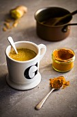 Mug filled with golden ginger milk with cinnamon, turmeric and honey on a light natural stone background with a teaspoon of turmeric and copper saucepan