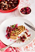 Grilled slices of halloumi on a white plate with pomegranate salsa and mint sprig on a patterened white tablecloth with kalamata olives in the background