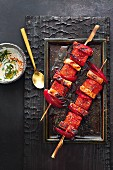 Grilled melon shashlik skewers with marinated pork belly and yoghurt and mint sauce