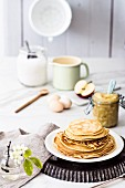 Stacked pancakes and a glass jar of apple sauce