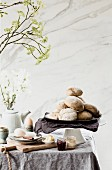 Fresh bread rolls on a breakfast table with eggs, honey and jam