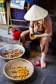 A woman peeling fresh turmeric in Hoi An, Vietnam