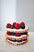 Stacks of wafer cookies, icing and mixed berries with a white background