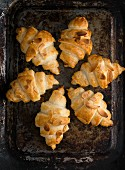 Croissants with almond flakes on a baking sheet