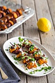 Vegetarian paprika sweet potato kebabs on skewers with red onions, barbecued and drizzled with lemon tahini sauce