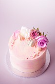 Pink marbled celebration cake decorated with flowers, macarons and petals