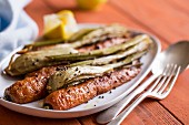 Fennel and carrot roasted with mustard seeds and lemon half squeezed on a white plate