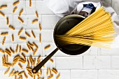 Aged saucepan with uncooked spaghetti and fusilli on a white tiled background wtih a teatowel