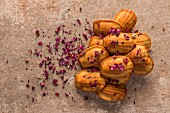 A pile of spelt madeleines with rosewater, scattered with edible rose petals, on a natural aged stone background