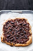 Spelt puff pastry pissaladiere with caramelised onions, anchovies and olives on a piece of baking paper on an aluminium metal tray