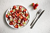 Strawberry, avocado, feta and a strawberry balsamic dressing on a white plate and a white background with cutlery and strawberrys