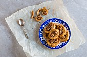 A white plate with blue decoration stacked with sweet cinnamon palmiers on a piece of baking paper and a teaspoon on a light grey natural stone background