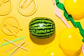 Watermelon with yellow plates, tablecloth, cutlery and balloons, along with streamers and straws