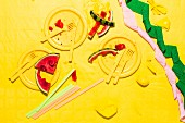 Watermelon pieces with yellow plates, tablecloth, cutlery and burst balloons, along with streamers and straws