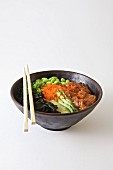 Poke bowl with salmon, edamame, seaweed and sesame oil