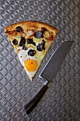 A slice of pizza with egg and black truffle on a stainless steel surface