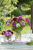 Sträuße aus Dianthus barbatus (Bartnelken) und Galium verum (Labkraut), Zopf aus Gras um Glas gebunden
