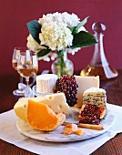A still life with cheese, fruit and wine