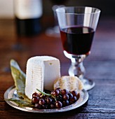 A still life with cheese, grapes and red wine