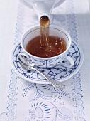 Ostfriesentee zubereiten: Tee in die Tasse gießen