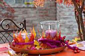 Einmachglaeser zweckentfremdet als Windlichter mit buntem Herbstlaub