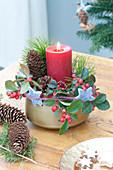 Kleines Adventsgesteck mit roter Kerze, Zweigen von Pinus ( Kiefer
