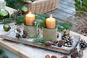 Kerzendeko in Bechern mit Gold-Dekor auf Holzbrett im ersten Schnee