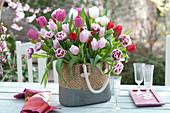 Üppiger Strauß aus gemischten Tulipa ( Tulpen ) in Flechttasche