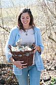 Frau bringt Weidenkorb mit Ostereiern und Osterhase als Osternest