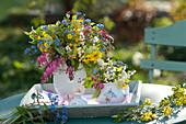 Bunte Frühlingssträuße in Kännchen auf Holz-Tablett :