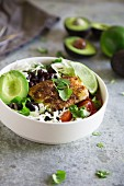 A taco bowl with fish, avocado, black beans, and white cabbage