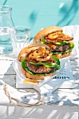 Grilled hamburgers with avocado and onions