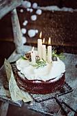 Christmas chocolate cake with lit candles