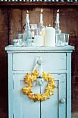 Mürbteigkranz und Kerzen auf einem Vintage-Schrank