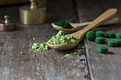 Spirulina tablets and spirulina powder on wooden spoons