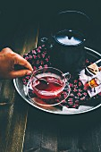 A teapot and glass teacup with herbal tea on a tray