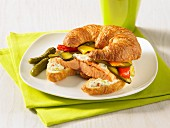 Salmon burger pickles hot peppers on a croissant