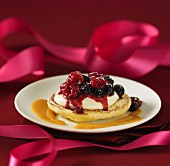 Blini topped with cream and berries