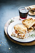 A panini with porchetta and a glass of red wine