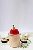Paprika-Brotaufstrich im Glas und auf Pumpernickel