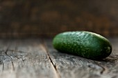 A cucumber on a wooden background (close up)