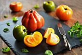 Colourful rustic tomatoes on a chopping board with an old knife and various herbs
